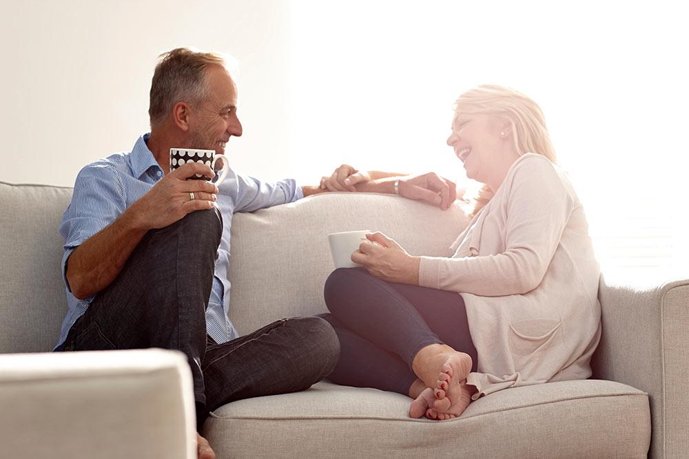 Paar, ca. 50 Jahre alt, sitzt lachend auf der Couch.